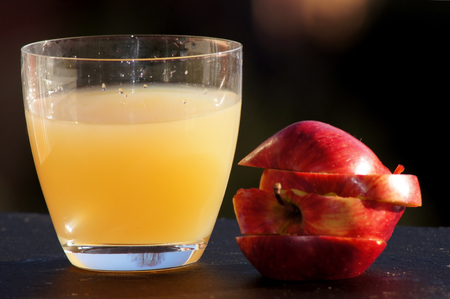 Apple juice in a glass with fresh apple