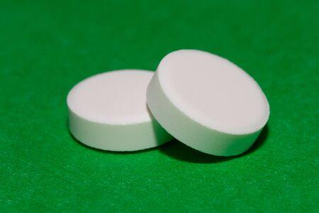 white pills on a green background. Bottle, blister Zdjęcie Seryjne