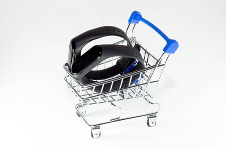 Two fitness bracelets in a shopping trolley on a white background
