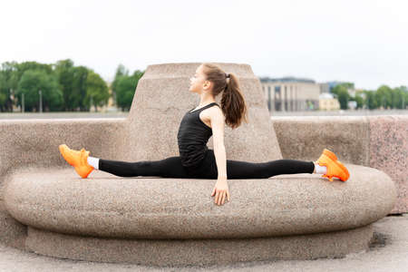 Girl gymnast performs exercises on the waterfront against the background of the river and the park. Series of photos