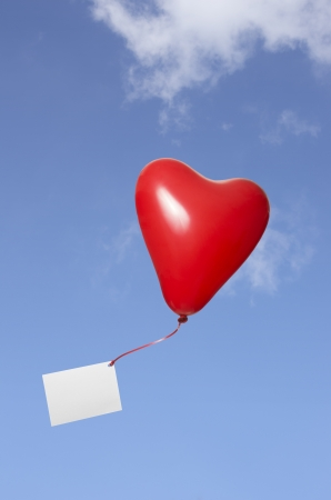 red floating heart balloon with  greeting card in the sky photo