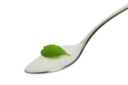 teaspoon with filled with sugar and a stevia leaf  photo