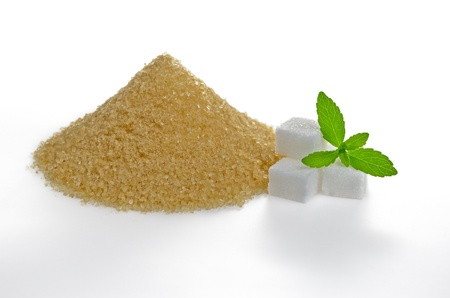 Stevia leaves with sugar cubes and a brown sugar heap photo