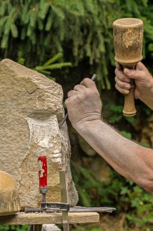 scultore che lavora su una scultura in pietra