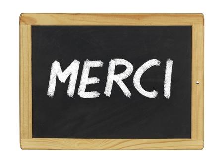 french text: Merci written on a blackboard