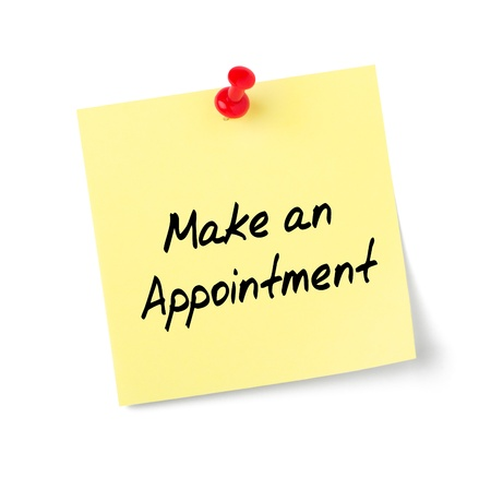 written date: Yellow paper note with text Make an Appointment Stock Photo