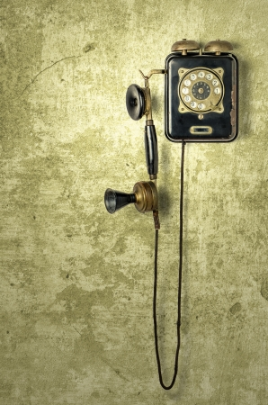 antique telephone on a grungy yellow wall photo