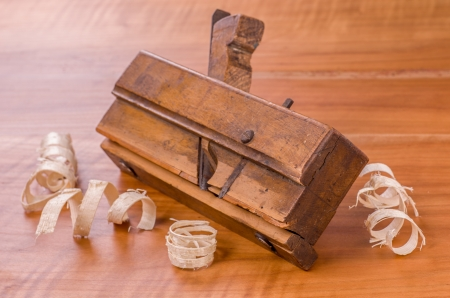 wood molding: old molding plane with shavings on a cherry wood board
