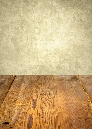 table surface: antique wooden table in front of weathered wall Stock Photo