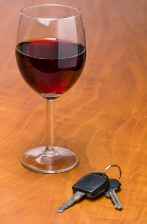 Red wine glass with car keys photo