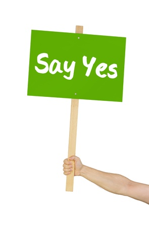 Person holding a sign saying Say yes photo