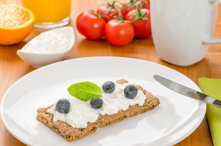 crispbread: Pane croccante con crema di formaggio e mirtilli su un tavolo per la colazione