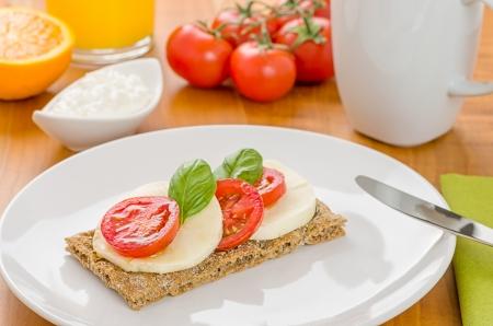 Crispbread with tomato and mozzarella on a breakfast table photo