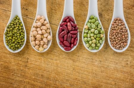 렌즈 콩: 도자기 숟가락에 여러 가지 콩과 식물 스톡 사진