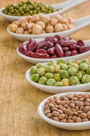 leguminosas: Varias legumbres en las cucharas de porcelana