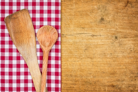 Rustic wooden background with checkered tablecloth and wooden spoon photo
