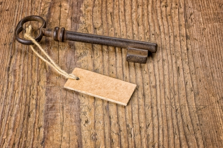 Old key with a tag on a wooden board photo