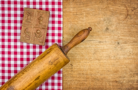 menue: Rolling pin with mold on a wooden board with a checkered tablecloth