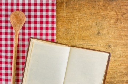 Wooden spoon and book on a wooden board with a checkered tablecloth photo