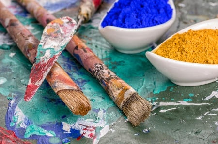pigments: Brush, spatula and color pigments on a wooden palette
