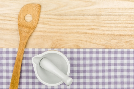 menue: Wooden spoon and mortar on a purple checkered table cloth on a wooden background