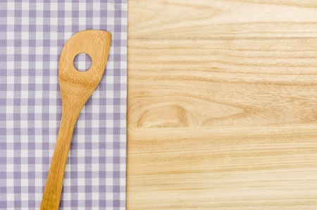 menue: Wooden spoon on a purple checkered table cloth on a wooden background Stock Photo