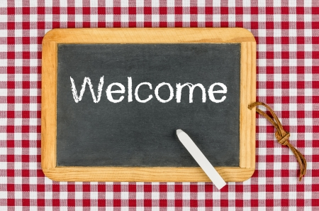 red tablecloth: Blackboard with text Welcome on a checkered tablecloth