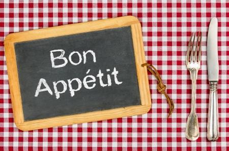 Blackboard mit dem Text Bon Appetit auf einem karierten Tischtuch