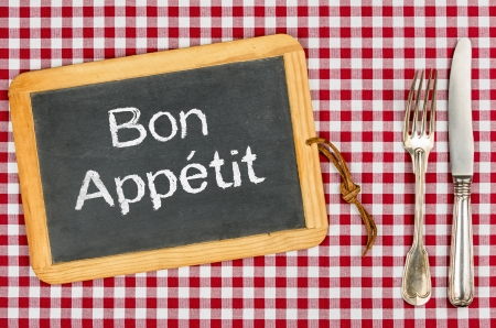 Blackboard with the text Bon Appetit on a checkered tablecloth photo