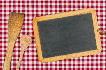赤の市松模様のテーブル クロスに木製のスプーンで空の黒板 写真素材