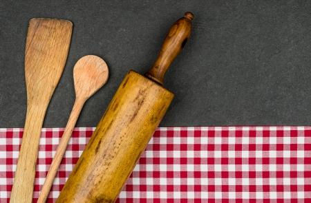 manteles: Rodillo con la cuchara de madera en una placa de la pizarra Foto de archivo