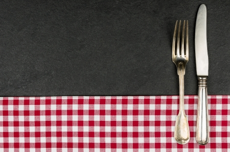 Silverware on a slate plate with a red checkered tablecloth photo