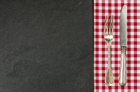 tablecloth: Silverware on a slate plate with a red checkered tablecloth