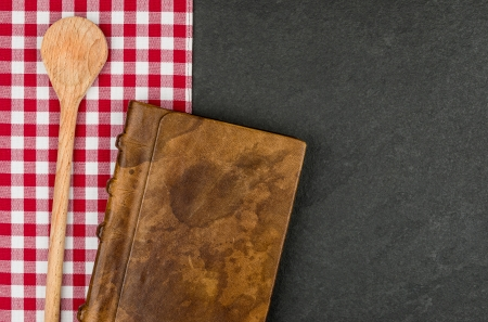 Wooden spoon and coockbook on a slate plate  photo