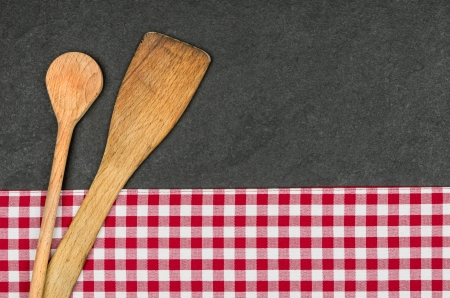 Wooden spoon on a slate plate with a red checkered tablecloth photo