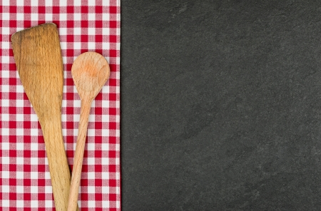 dishcloth: Wooden spoon on a slate plate with a red checkered tablecloth Stock Photo
