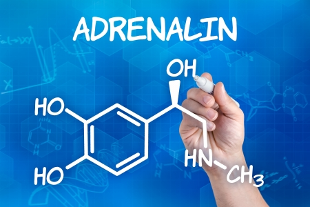 adrenalin: hand with pen drawing the chemical formula of adrenalin