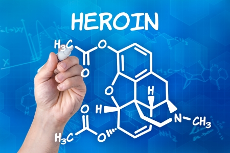 heroin: hand with pen drawing the chemical formula of heroin