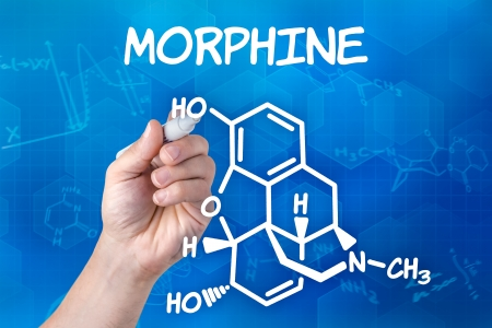 morphine: hand with pen drawing the chemical formula of Morphine