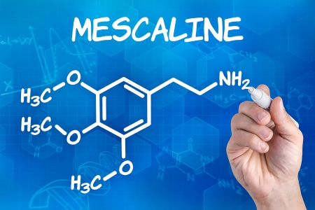 mescaline: hand with pen drawing the chemical formula of mescaline