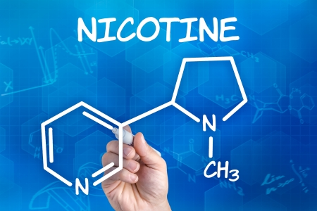 nicotine: hand with pen drawing the chemical formula of nicotine Stock Photo