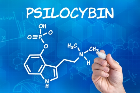 hallucinogen: hand with pen drawing the chemical formula of psilocybin