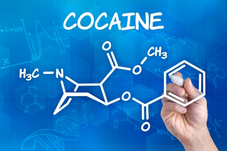 drug addiction: hand with pen drawing the chemical formula of cocaine Stock Photo