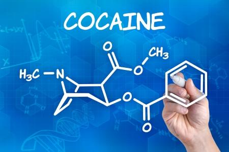 drogadiccion: mano con lápiz el dibujo de la fórmula química de la cocaína Foto de archivo
