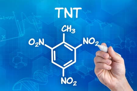 tnt: hand with pen drawing the chemical formula of  TNT