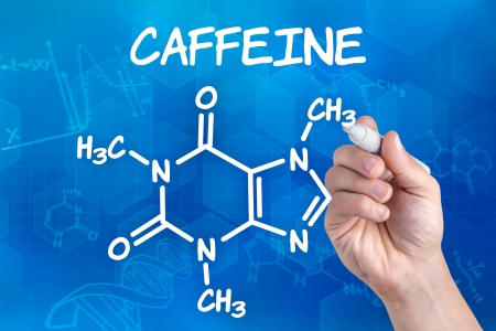alkaloid: hand with pen drawing the chemical formula of Caffeine