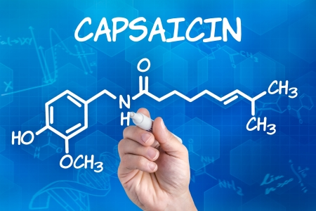 capsaicin: hand with pen drawing the chemical formula of capsaicin