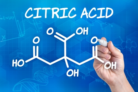citric: hand with pen drawing the chemical formula of citric acid