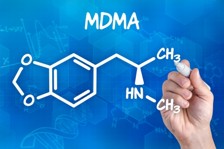hand with pen drawing the chemical formula of MDMA photo
