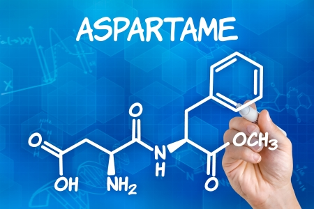 sweetener: Hand with pen drawing the chemical formula of aspartame
